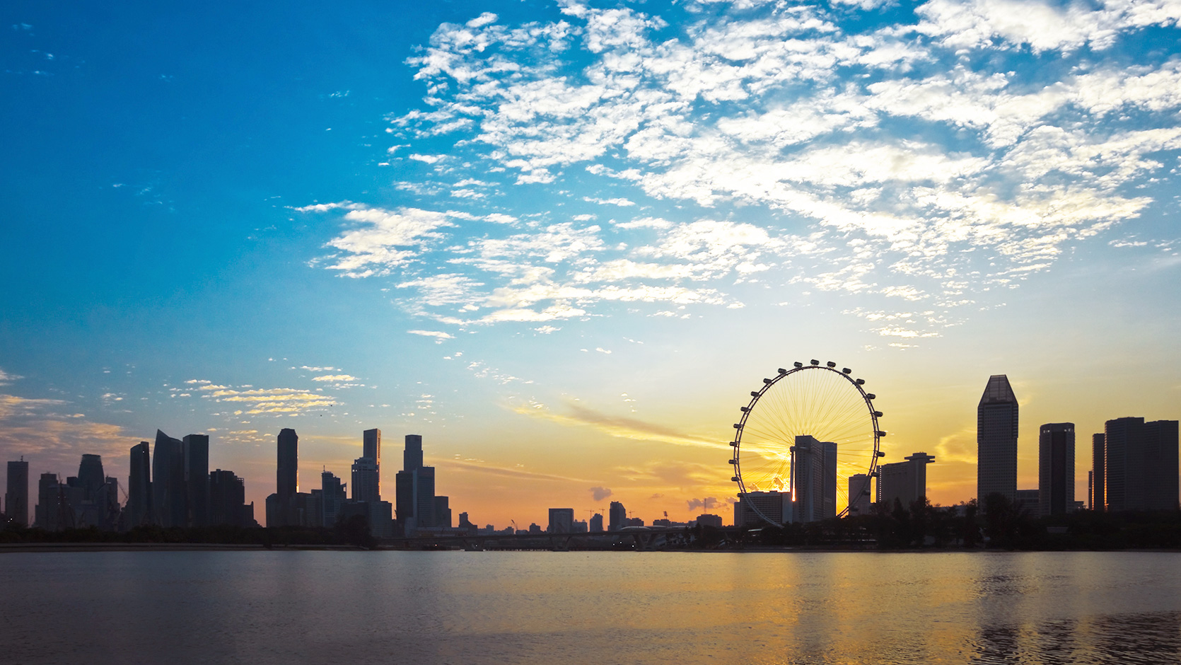 Sunrise silhouette of the Singapore CBD skyline, featuring the Singapore Flyer
