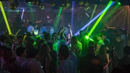 Party goers dancing amidst green lights at Zouk