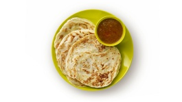 A plate of roti prata with curry on the side