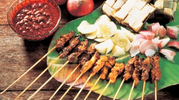 Sticks of satay, onions, ketupats on a plate with satay sauce by the side