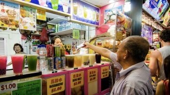 An elderly man buying drinks from a streetside drinks stall at Bugis Street