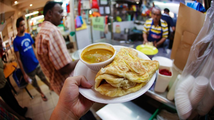 A plate of roti prata with curry on the side.