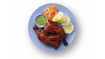 A plate of tandoori chicken with mint chutney