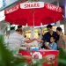 Young family buying ice-cream from a roadside vendor outside Orchard Road, Wisma Atria