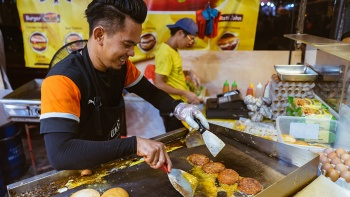 Close up candid shot of a vendor at a <i>pasar malam</i> preparing the famous Ramly burgers over the grill
