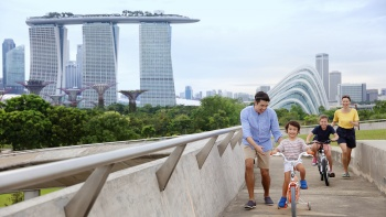 Family with 2 young children cycling at Marina Barrage against the Marina Bay Sands and Gardens by the Bay backdrop