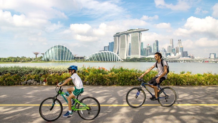 a parent and child cycling with the Marina Bay skyline in the background