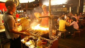 Exterior night shot of men barbequing satay with people dining