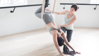 A Yoga instructor coaching a Yogi at Aerial at Upside Motion