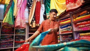 An Indian man laying out colourful saris for display at Little India Arcade
