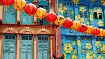 A line of red and orange lantern lined up at Chinatown with a shophouse backdrop