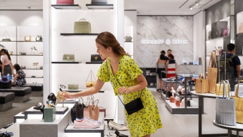 Wide shot of a lady picking up a shoe in a Charles & Keith store