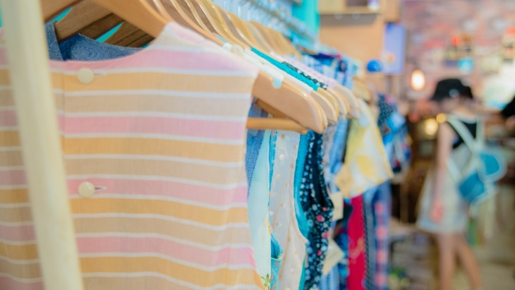 Woman browses a rack of colourful clothes
