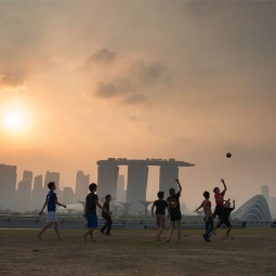 Boys playing soccer at Marina Barrage at dusk, with the misty silhouette of Marina Bay in the background