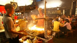A tourist looking at a street hawker making satay over a flame at Lau Pa Sat