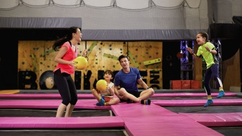 Interior action shot of family playing ball at Bounce Singapore
