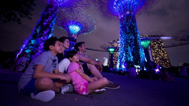 A family entertained by the colourful lights from the Supertrees at night