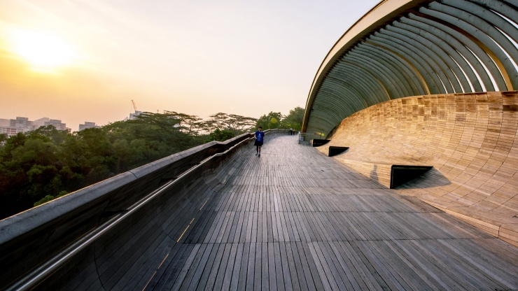 A boy walking on the Henderson Waves Bridge during the golden hour