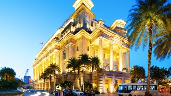 The exterior of The Fullerton Hotel at dusk.