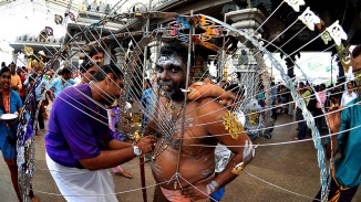 An Indian man assisting another to dress up in the symbolic skewers for Thaipusam procession.