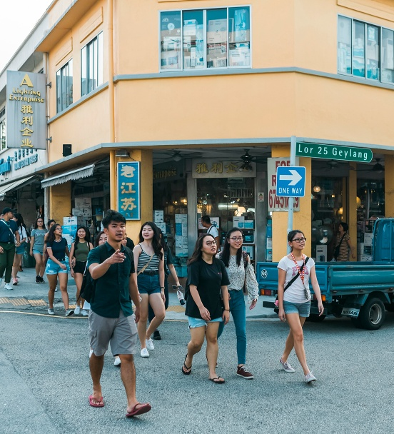 Cai Yinzhou and his tour group walking along the streets of Geylang Lorong 25