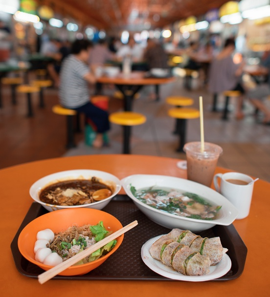 A bokeh shot of hawker food against the backdrop of a hawker centre