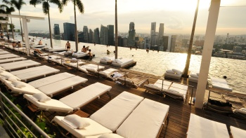 Marina Bay Sands<sup>®</sup> SkyPark infinity pool overlooking the Singapore skyline in the day