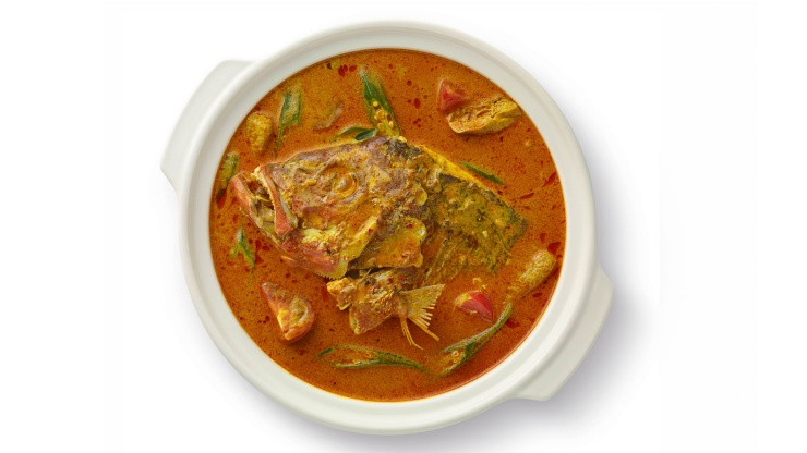 Flat lay of a pot of fish head curry cooked with vegetables and spices
