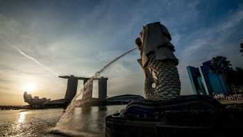 Sunset wide angle shot of Merlion looking out to Marina Bay Sands and ArtScience Museum