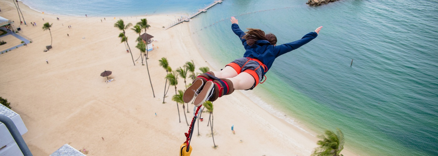 Woman leaping off AJ Hackett bungee, with Sentosa beach backdrop
