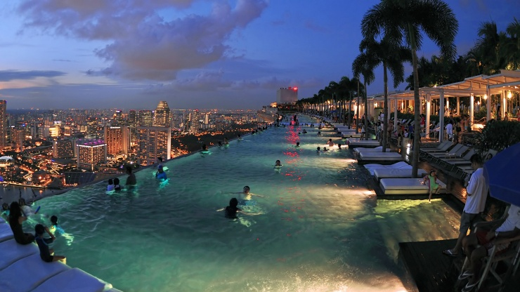 Marina Bay Sands<sup>®</sup> SkyPark infinity pool overlooking the Singapore skyline at night