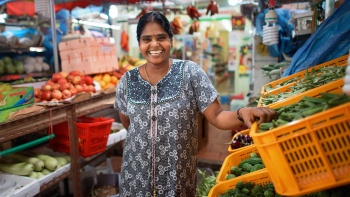 A portrait shot of a vegetable stall owner in Little India