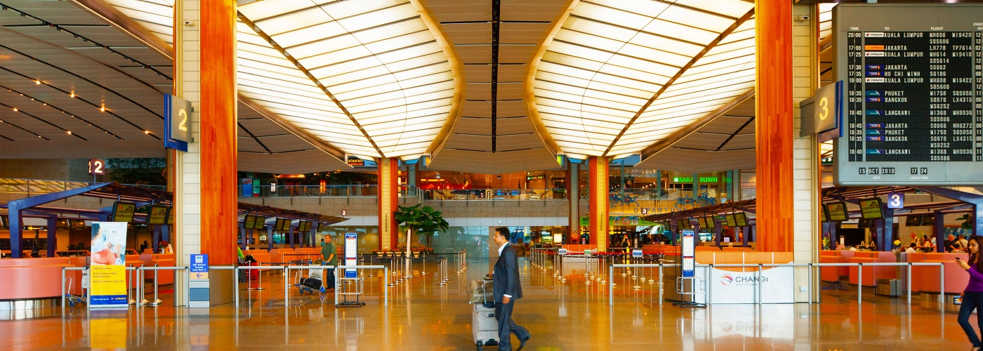 Man in suit with suitcase walking pass baggage and ticket counters in Singapore Changi Airport