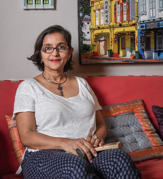 Ruqxana Vasanwala sitting on the couch at her home.