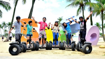 Tour goers on Segway scooters at Siloso Beach, Sentosa