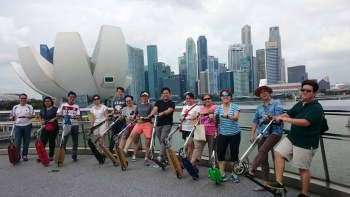 City by the Water kick-scooter tour participants pose on the Helix Bridge overlooking the Marina Bay skyline