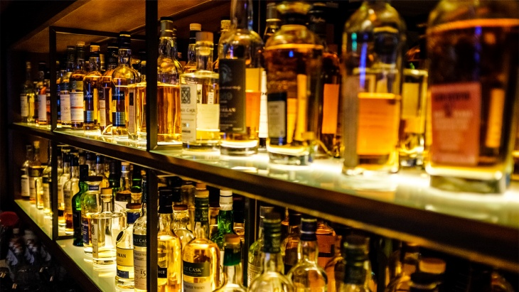 A shelf of different types of whisky and other alcoholic beverages.