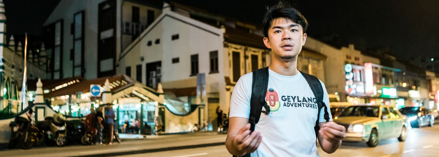 Cai Yinzhou introduces the night life of Geylang to a tour group.