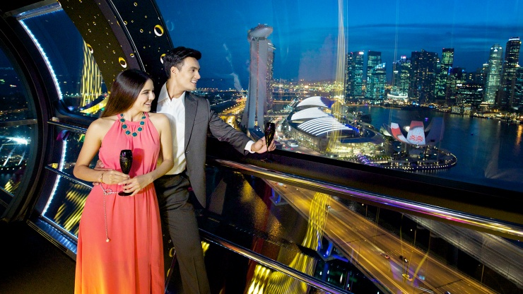 A couple viewing the Singapore skyline in the evening from a Singapore Flyer cabin