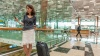 Lady at Changi Airport with a mobile phone and luggage