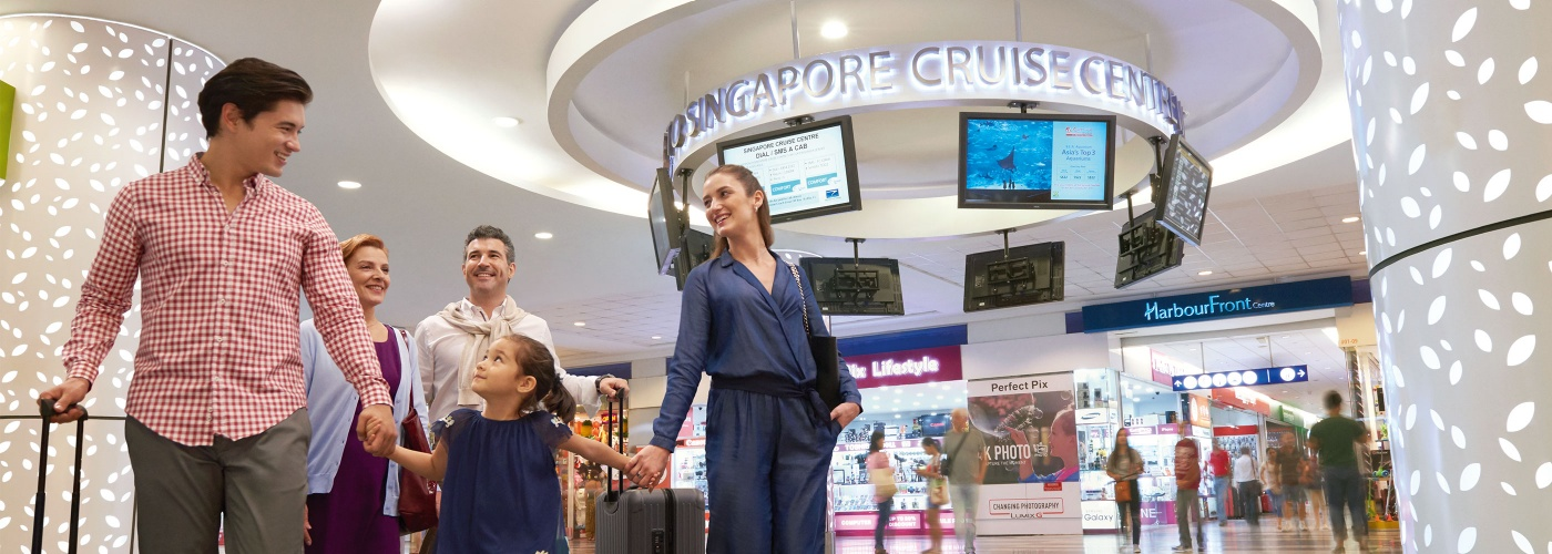 Family of five with lugguage walking across lobby of Sinagpore Cruise Center