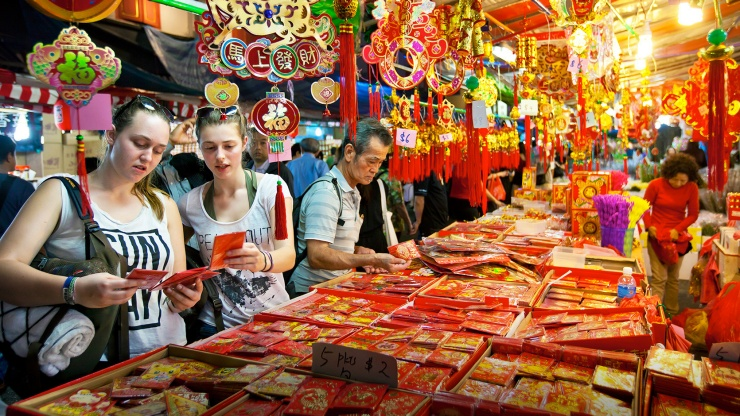 Wide shot of tourists buying red packets at Chinatown