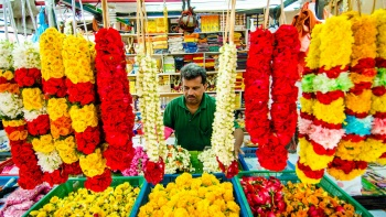 Close-up shot of a man selling flowers and garlands.