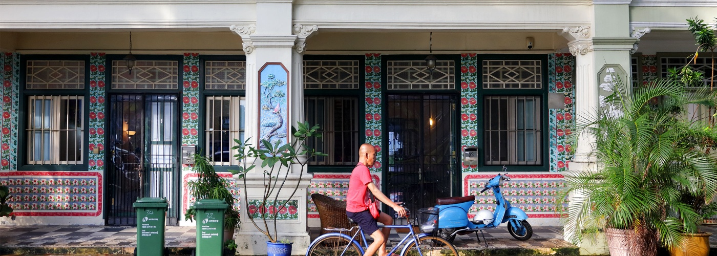 Man cycling past heritage shophouses at Jalan Besar, Singapore
