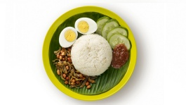 A plate of nasi lemak with fried fish, cucumber, nuts, eggs and sambal chilli