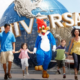 A family of tourists posing with a character in front of the globe at Universal Studios Singapore™