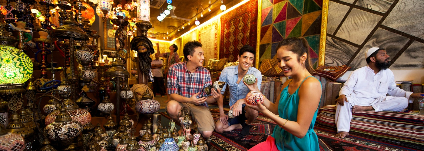 An interior view of a shop selling lampshades and carpets with people in the shop