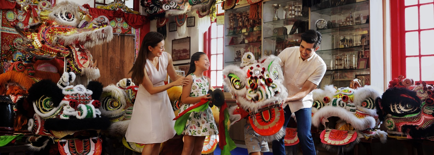 Family engaged in traditional lion dance at Kong Chow Wui Koon, Chinatown Singapore