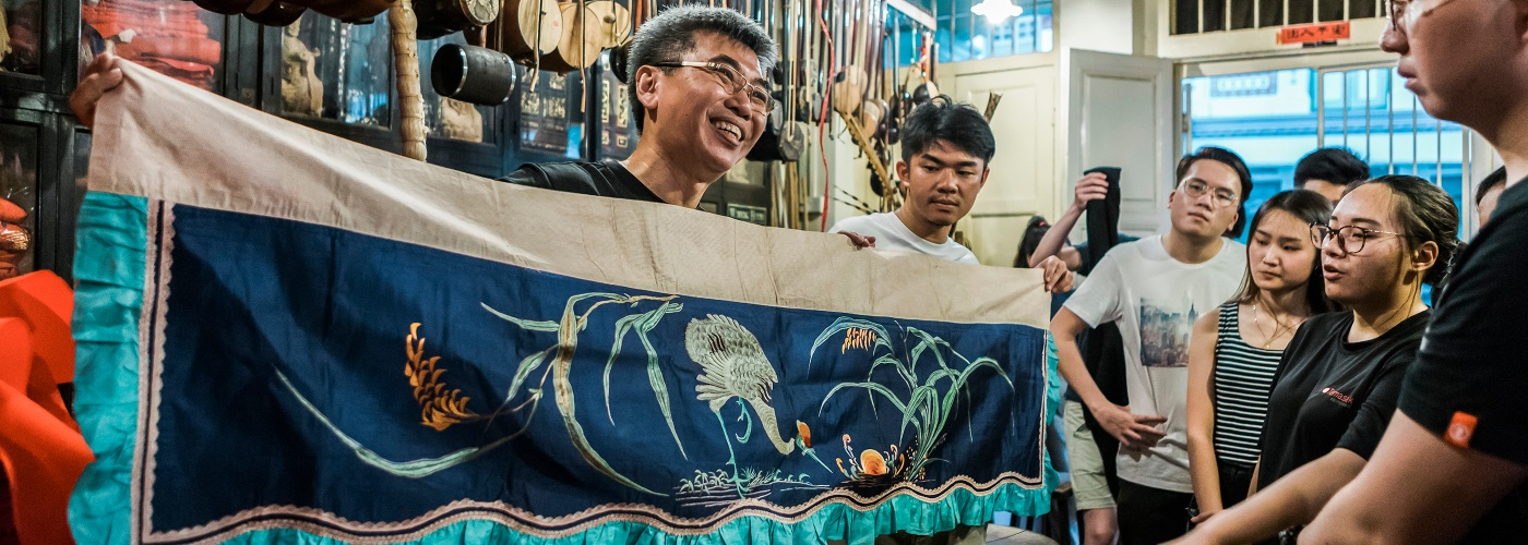 A man from Eng Tiang Huat Chinese Cultural Shop holding a banner introducing Chinese culture and tapestry