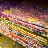 A neatly stacked variety of batik fabric from Royal Fabrics
